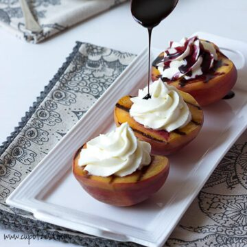 three halves of peaches, grilled and topped with mascarpone cream