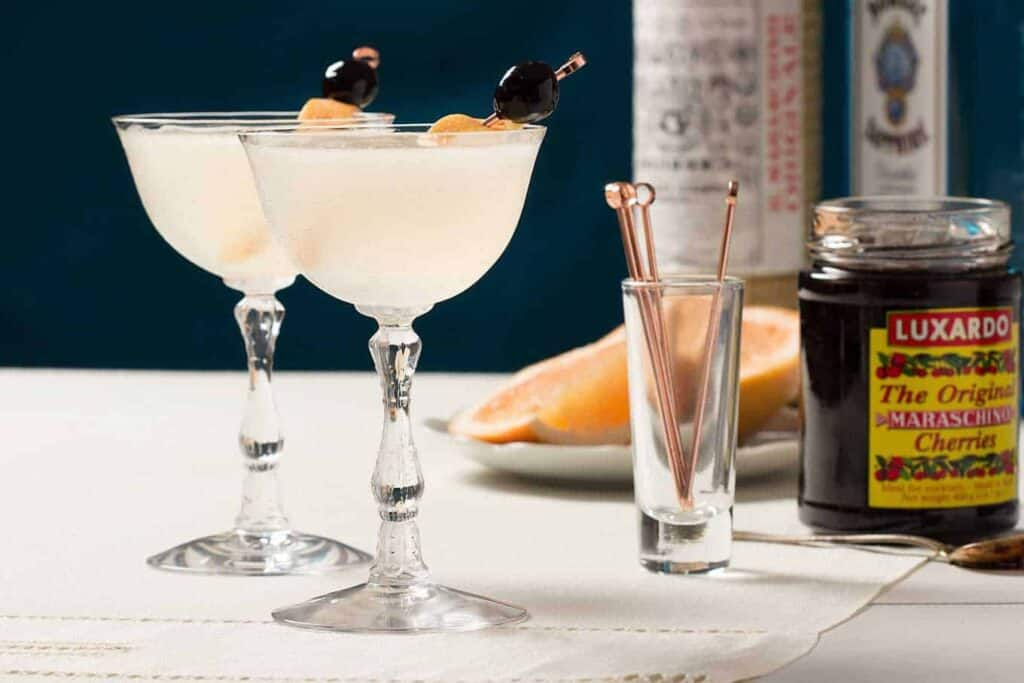 Horizontal image of two cocktail glasses filled with the seventh heaven cocktail and bottles of alcohol in the background