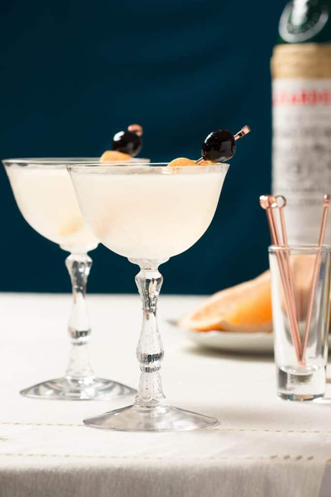 vertical image of two cocktails with an orange and luxardo cherrie garnish and cocktail picks in the background.