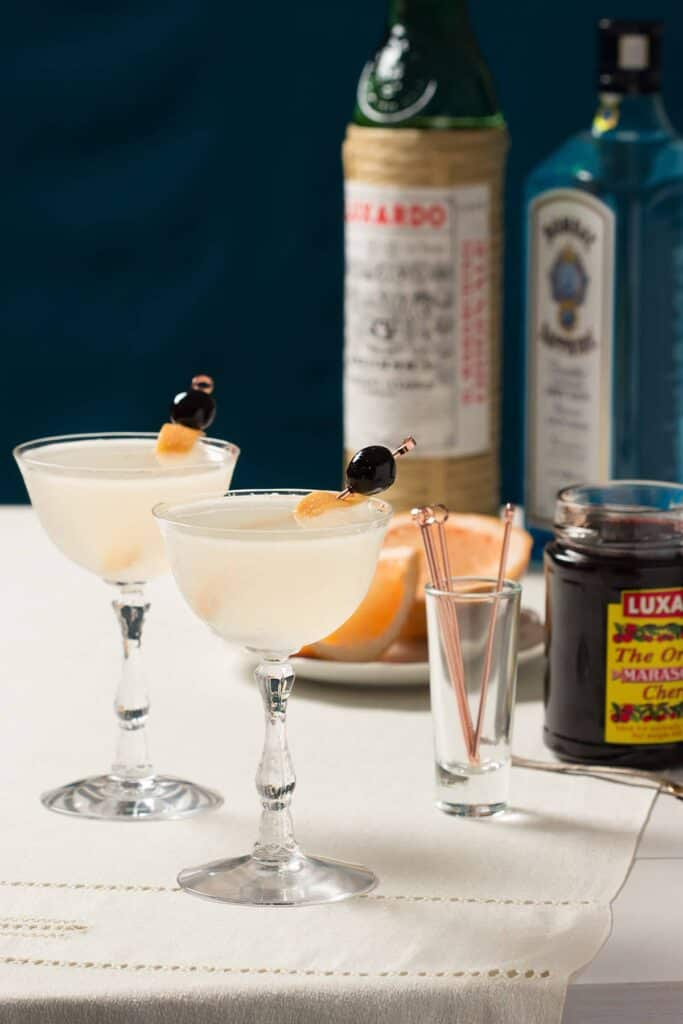 two classic cocktail classes filled with the seventh heaven cocktail and luxardo cherry garnishes. A bottle of gin, luxardo liqueur and cherries are in the background.
