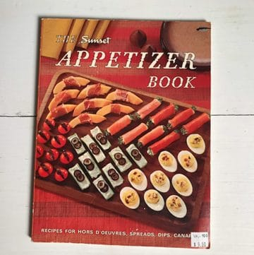 Cover of the 1960's Sunset Appetizer Cookbook laying flat on white surface horizontal