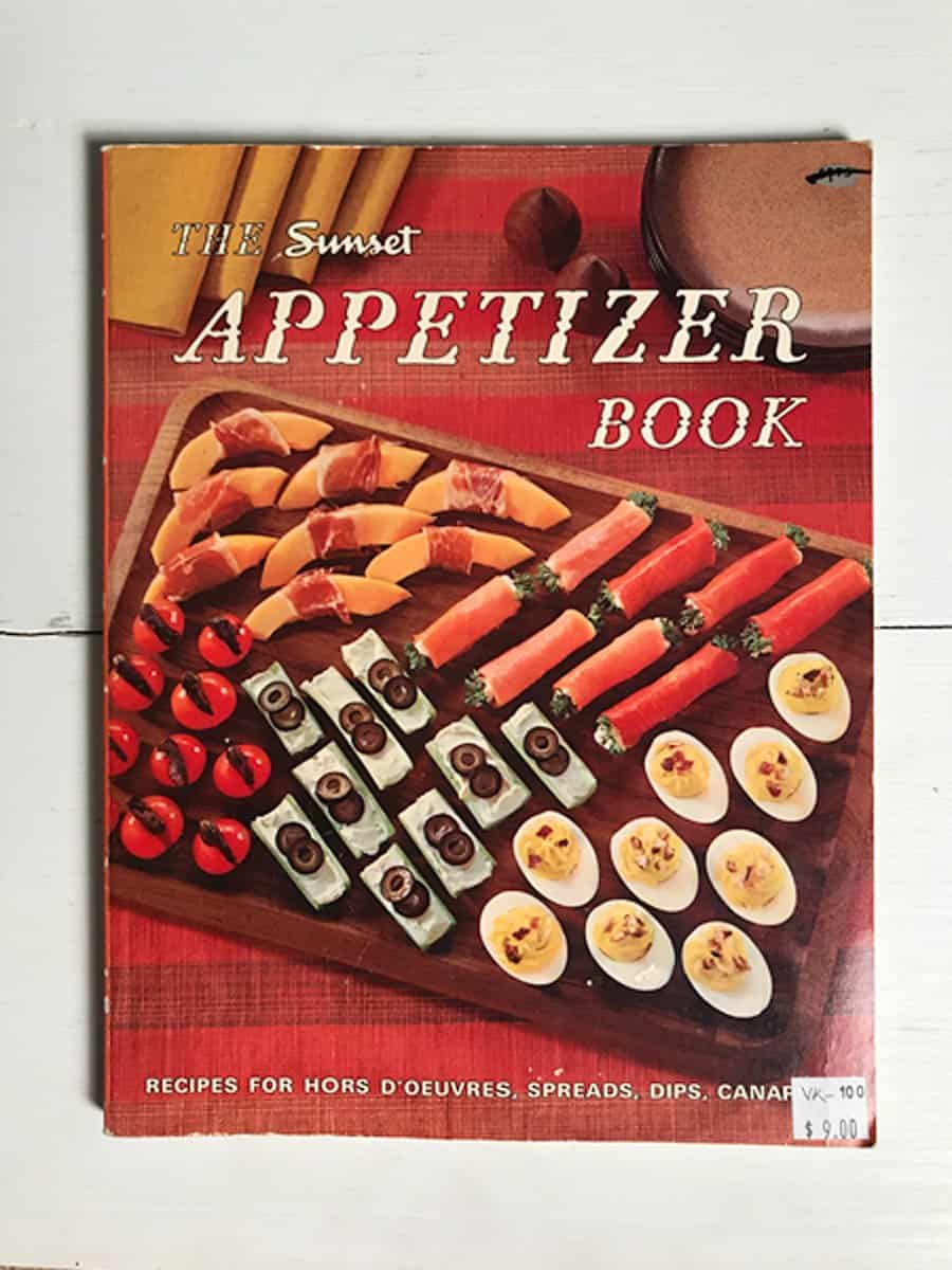 Cover of the 1960's Sunset Appetizer Cookbook laying flat on white surface vertical