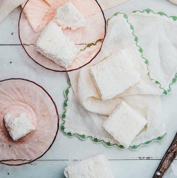 Two marshmallows on a white and green handkerchief next to two partially eaten marshmallows on pink plates.