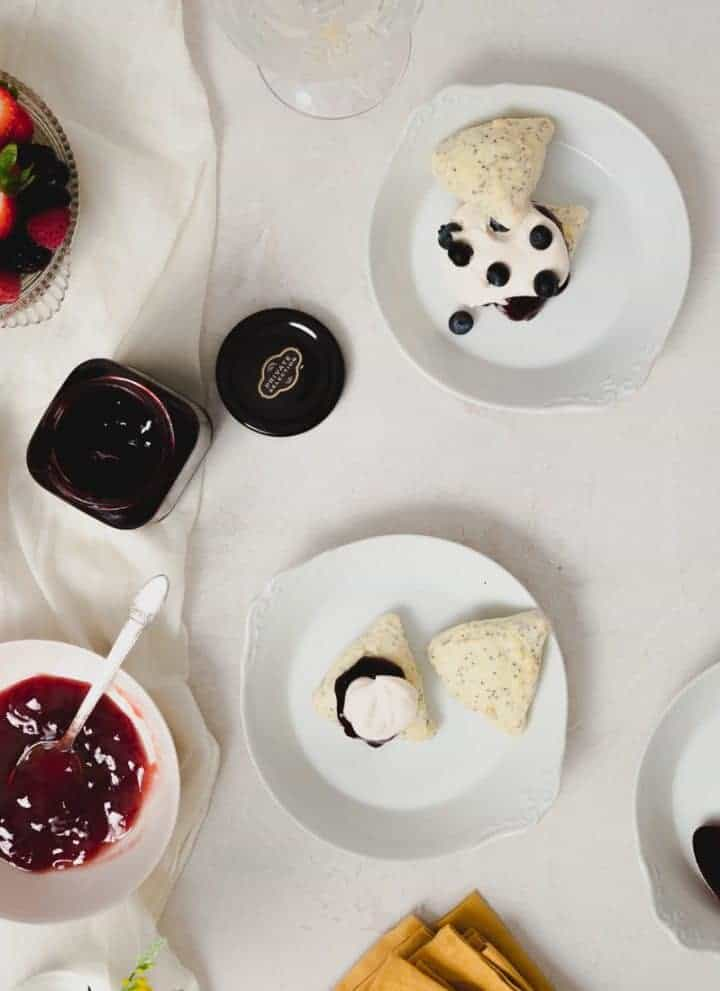 Square image of three white plates with two-bite scone shortcakes being assembled on them. Bowls of jam and berries are to the left of the assembled shortcakes.