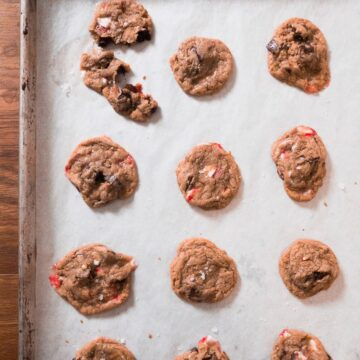 A baking sheet lined with parchment paper and multiple baked Chocolate Chunk Candy Cane Cookies on it.
