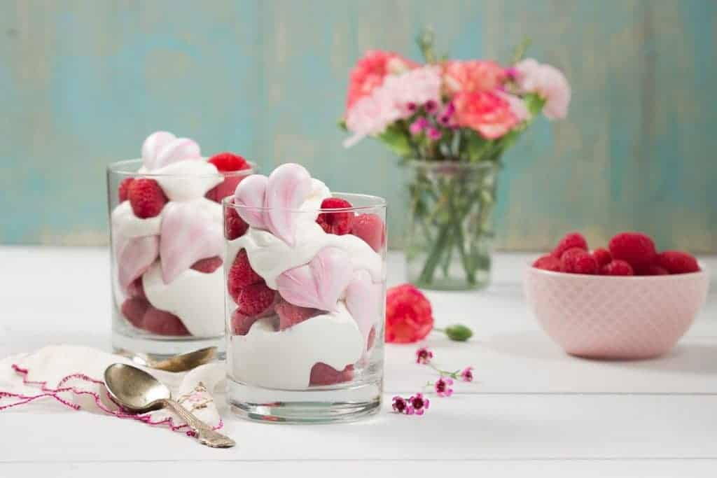 Two glass cups filled with whipped mascarpone cream and heart meringue cookies with a bowl of berries and flowers in the background.