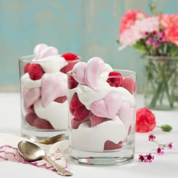Two glass cups filled with whipped mascarpone cream and heart meringue cookies with flowers in the background.