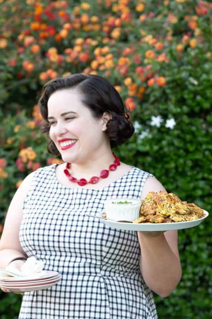 Woman with short brown heir standing, wearing red lipstick and smiling while outside holding a platter of baked zucchini fritters.