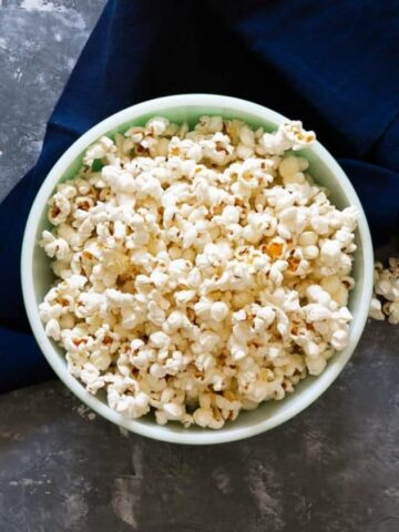 horizontal image of a bowl of popcorn on a dark blue napkin with popcorn on the surface