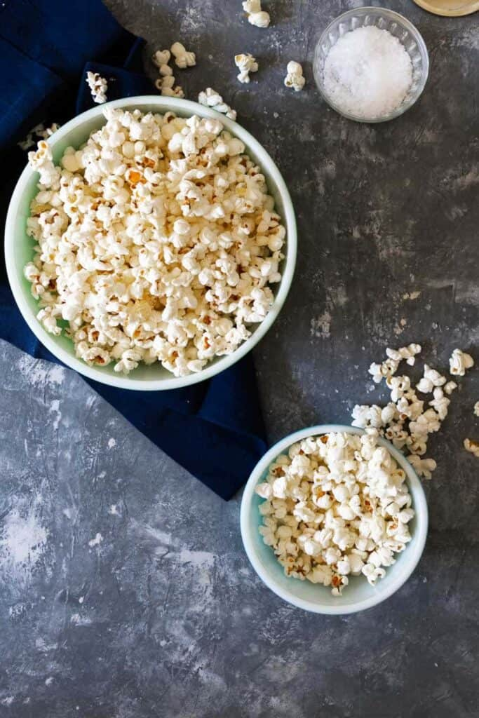 Vertical image of one large bowl of popcorn and a smaller bowl of popcorn with popcorn on the surface and a glass bowl of salt in the top corner