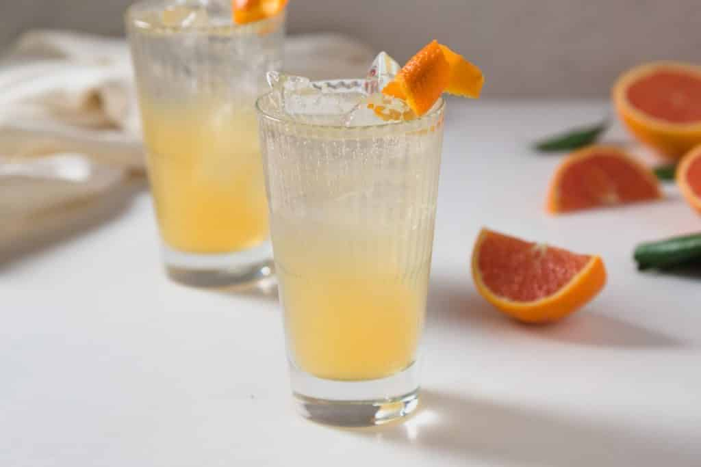 two orange colored cocktails with an orange twist as a garnish and wedgest of oranges in the background.