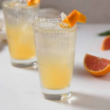two orange lemon gin cooler cocktails with orange colored liquid in the cocktail glasses with an orange twist as a garnish and wedges of oranges in the background.