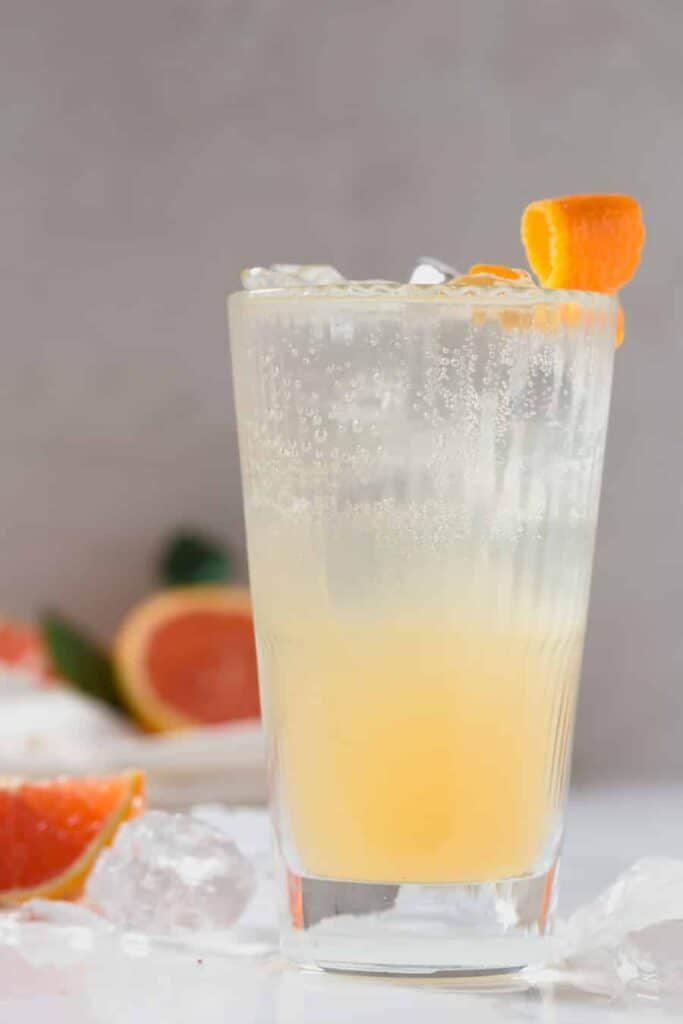 an orange lemon gin cooler cocktail that has orange colored liquid at the bottom of the glass and clear soda water at the top with an orange twist garnish