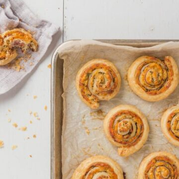 Horizontal overhead view of a parchment line baking sheet with baked puff pastry pinwheels on it and a broken pinwheel in the top left corner of the image.