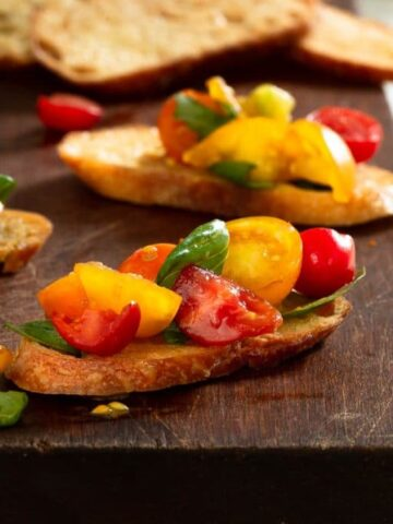vertical close up of a piece of toasted bread topped with a tomato basil and balsamic mixture on top of a wooden cutting board