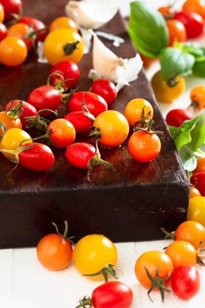 a large wooden cutting board with multi colored cherry tomatoes, garlic and basil on top and around it