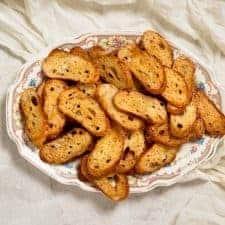 A few dozen baked crostini piled on an antique platter.