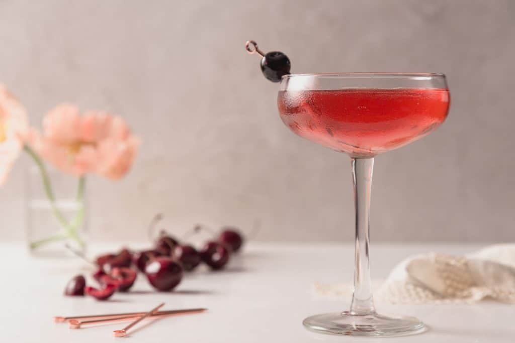 Kirsch Rose Cocktail Recipe - a deep red colored cocktail in a coupe glass with a luxardo garnish and cherries in the background