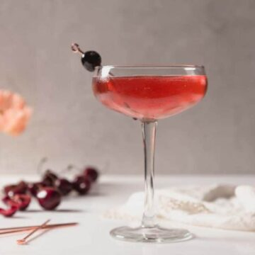 A Kirsch Rose Cocktail Recipe in in a coupe glass. The liquid is a deep red and there is a linen behind the glass and cherries to the left of it.