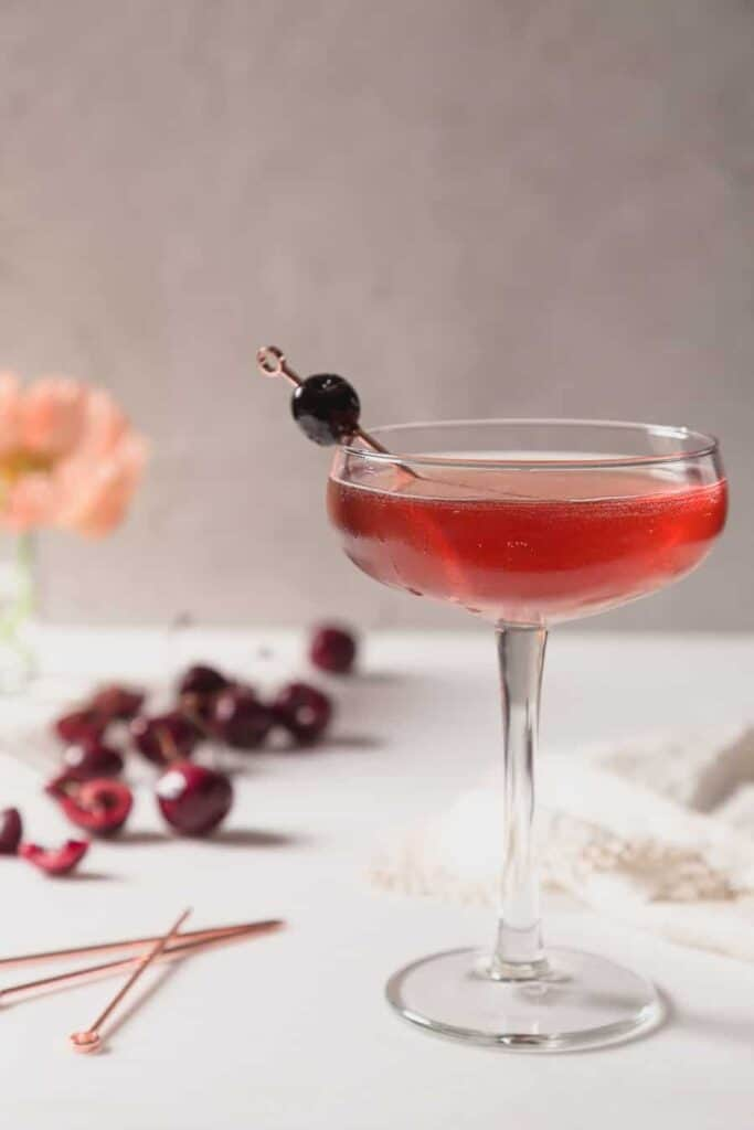 a close up of a deep red cocktail in a coupe glass with a luxardo cherry on a copper cocktail pic