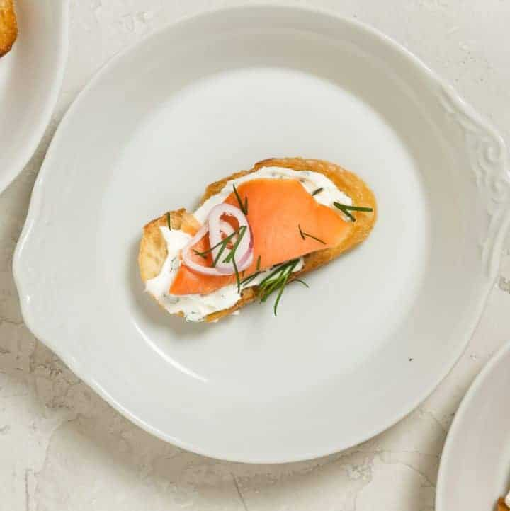 A white plate with a crostini topped with herb cream cheese, cold smoked salmon, thinly sliced shallots and dill.