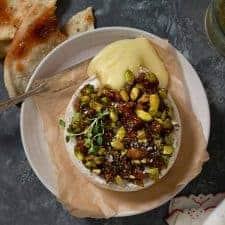 a wheel of baked brie with fig jam and pistachios on a plate. it's been cut into and oozing cheese.