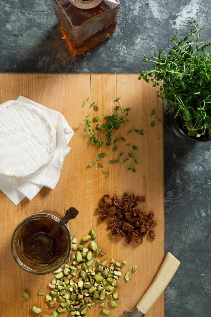Chopped pistachios and dried figs, a jar of fig jam and thyme leaves are on a wooden cutting board with a decanter of brandy and a thyme plant next to it.