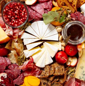 A vertical close up image of the fall meat and cheese board. There is a wheel of camembert cut into wedges in the middle, and surrounding it are crab apples, pomegranate seeds, aged gouda, a jar of honey and other charcuterie items on the board