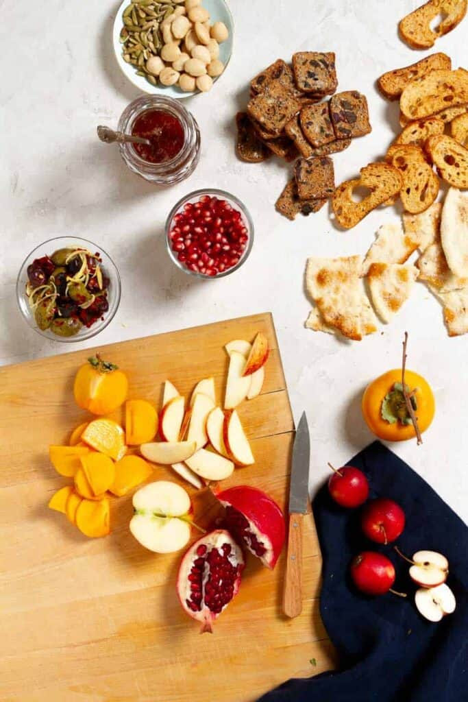 A light brown cutting board with sliced persimmons, apples, and wedges of pomegranates on it. There are also jars of olives, honey, and pomegranate seeds in the top of the image along with crackers and crostini on a light grey surface.