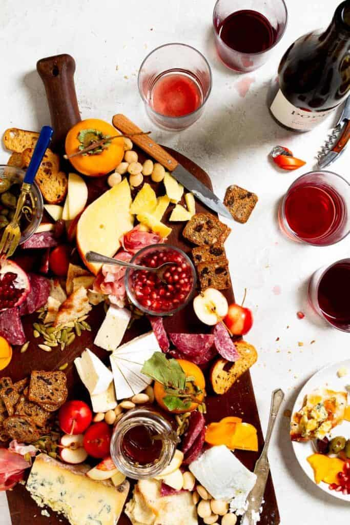 A large wooden cutting board with a variety of partially eaten cheeses, fall fruits, and charcuterie on it. There is a wine bottle and cups partially drunk from as if there was a party involving this cheese board.