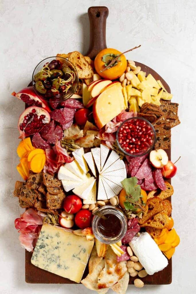 A cheese and charcuterie board fully assembled including persimmons, pomegranates, stilton, goat cheese, camembert, gouda and prosciutto among other tidbits.
