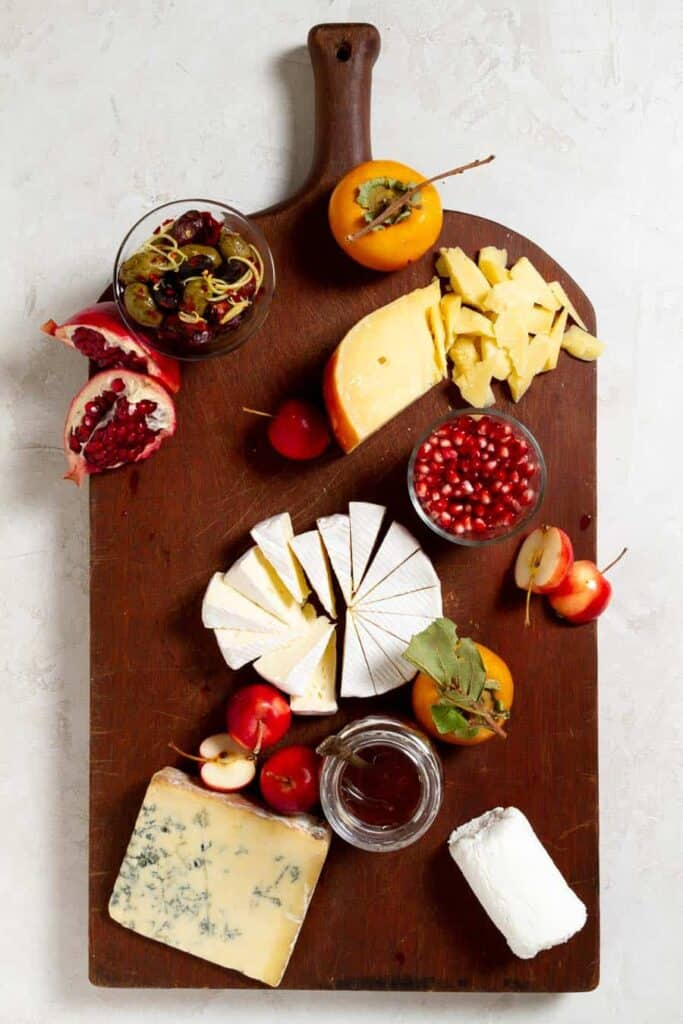 A cheese and charcuterie board in process of being assembled. On the board is four types of cheese, a jar of honey, and now crab apples, persimmons with leaves, and cut pomegranate wedges.