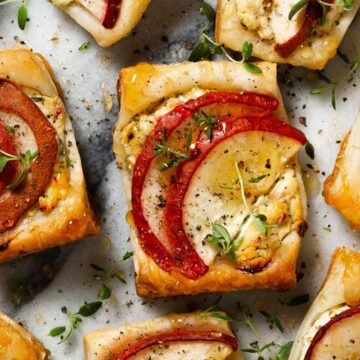 close up of mini puff pastry tarts that have goat cheese, pears, thyme and a honey drizzle on them