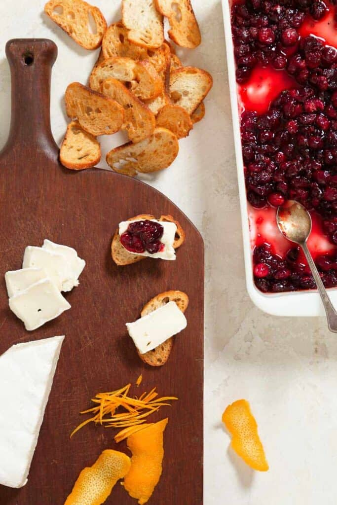 Cutting board with crostini being topped with brie and a cranberry sauce. There are orange peels and a wedge of brie on the board.