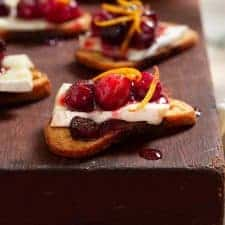 close up of a piece of crostini topped with a slice of brie, cranberry sauce and orange zest
