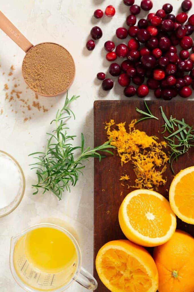 ingredients to make cranberry brie crostini on a light grey surface and brown cutting board. There are sliced oranges, orange juice, cranberries, sugars, rosemary and orange zest.