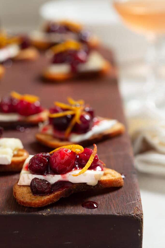 large dark wood cutting board topped with crostini topped with brie and cranberry sauce.