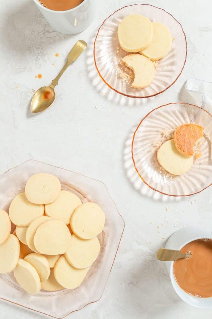 overhead of one large pink glass plate topped with a dozen of shortbread cookies. There are two other small glass plates with shortbread cookies and two mugs of coffee.