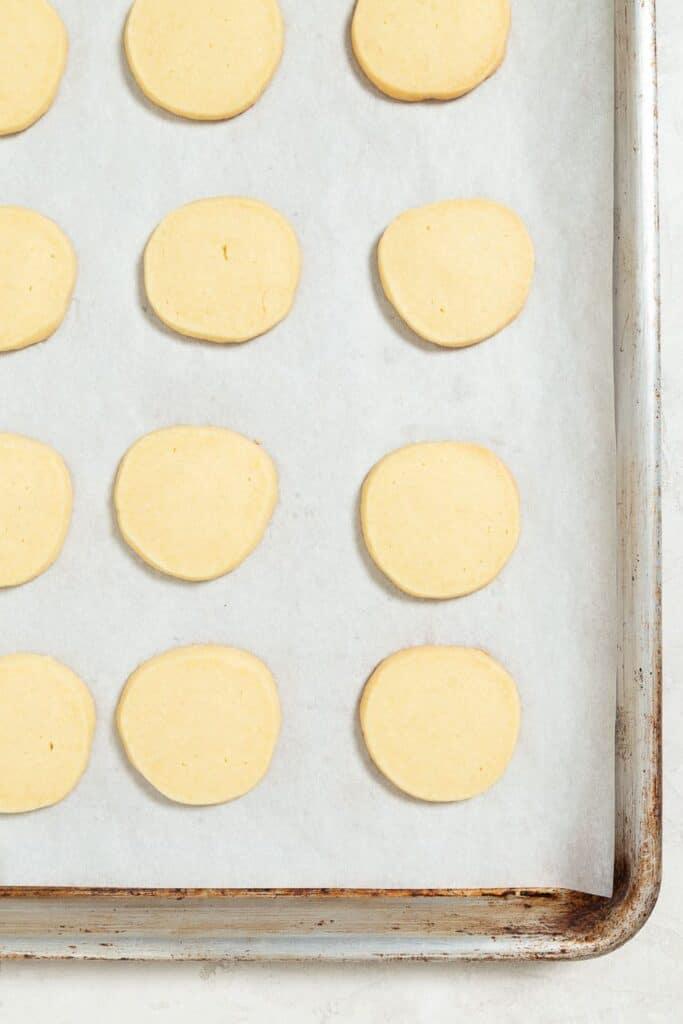 overhead image of a parchment lined baking sheet with fully cooked shortbread cookies on it.