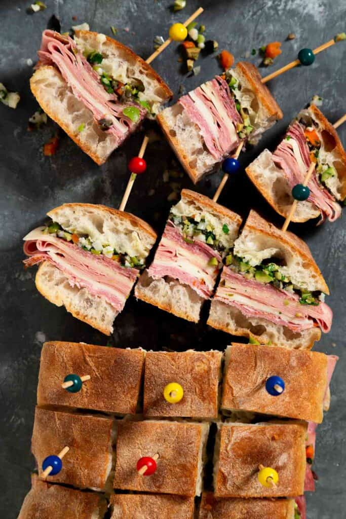 vertical image of multiple mini muffulettas with wooden picks holding them together. Six sandwiches are laying on their side  to see the layers of meat and olive salad.