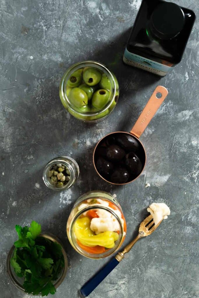 a bottle of olive oil, a jar of green olives, a measuring cup of black olives, capers, giardianra and parsley on a dark grey surface.