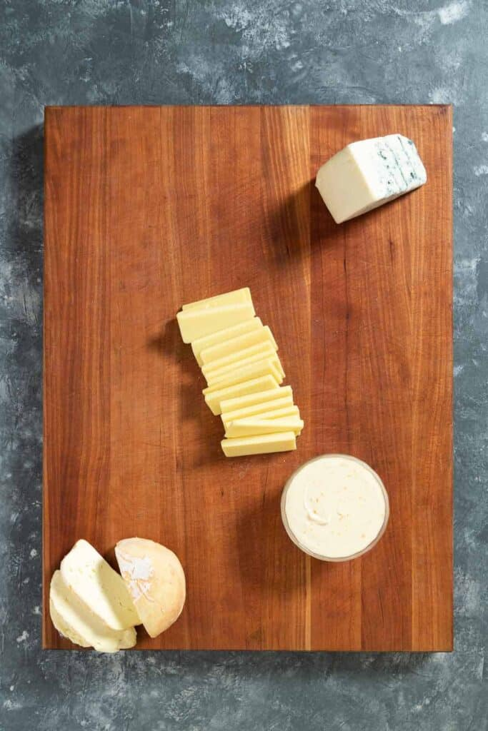 four different cheeses on a wooden cutting board