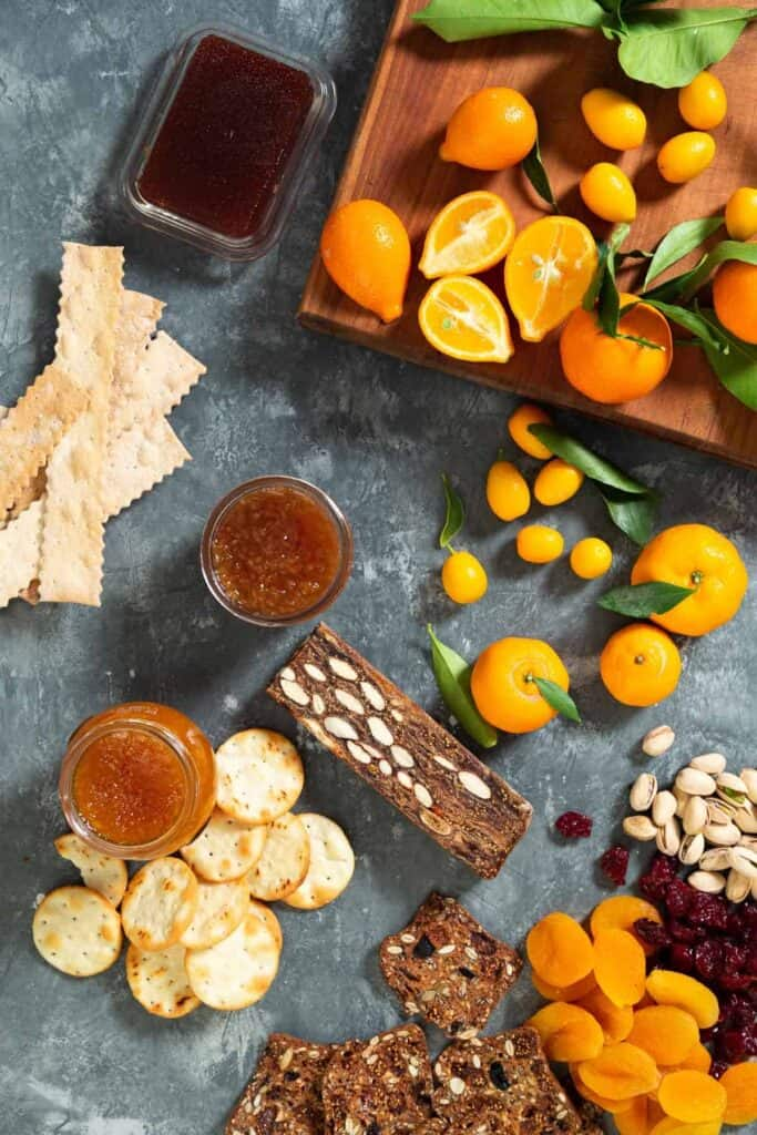 citrus, crackers, dried fruit and jam on a surface