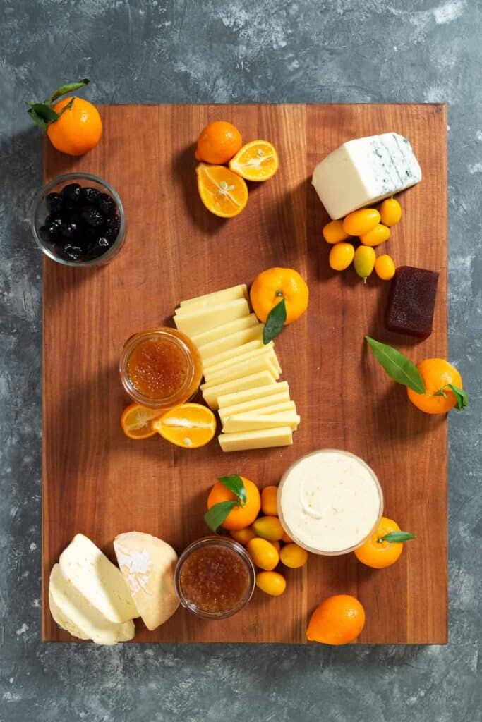 citrus, jams, olives and cheeses on a large wooden cutting board