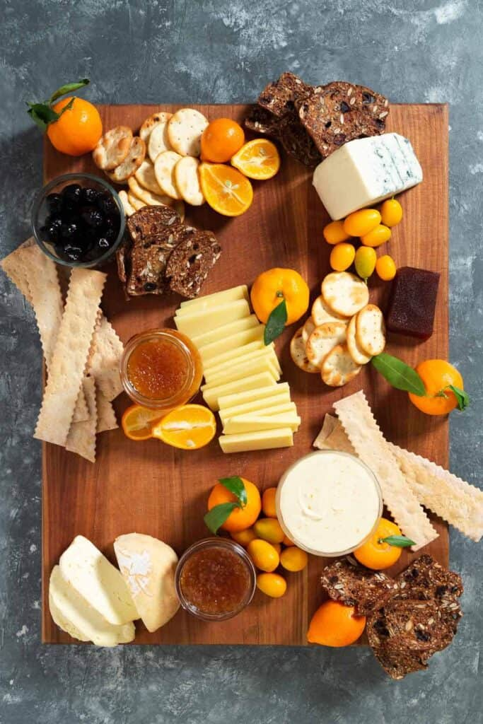 crackers, citrus, jams, olives, and cheese on a large wooden cutting board
