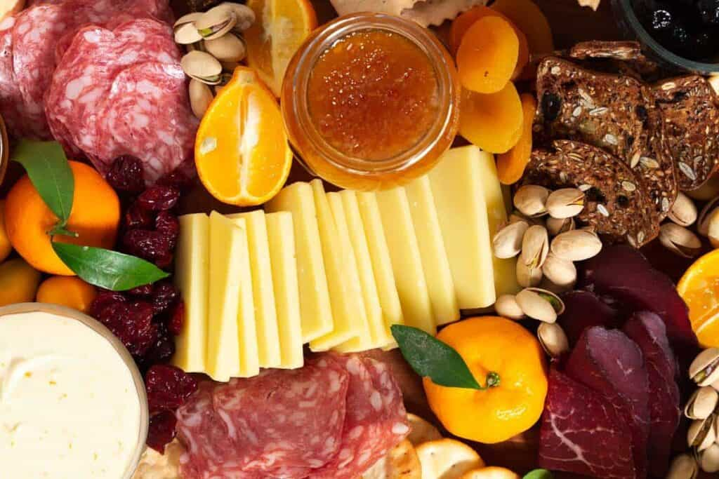 Sliced gruyere cheese surrounded by marmalade, citrus, salami, pistachios and nuts.