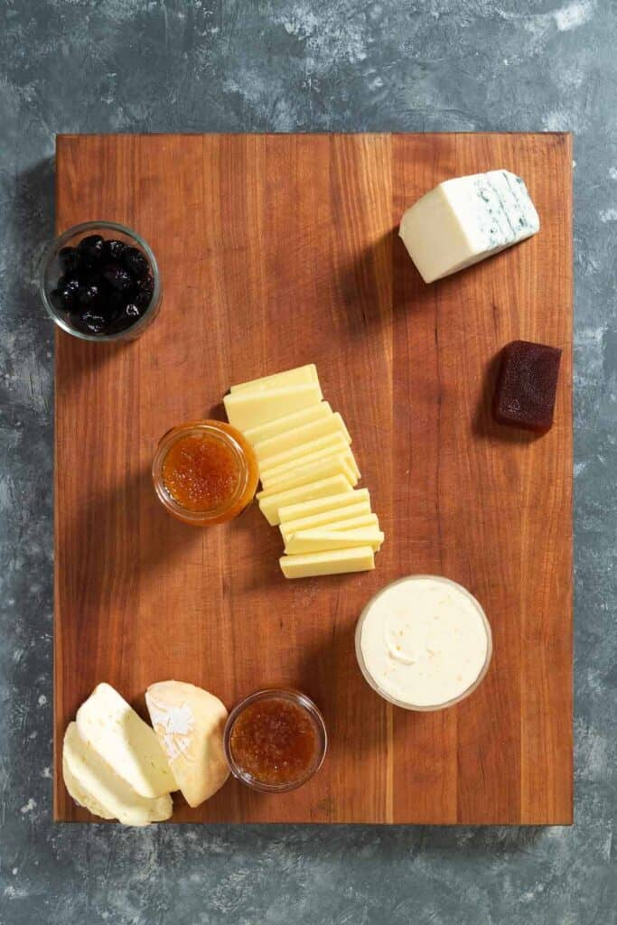 cheeses, jams, and olives on a large wooden cutting board
