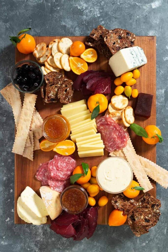 charcuterie, citrus, crackers, olives, jams on a large wooden cutting board