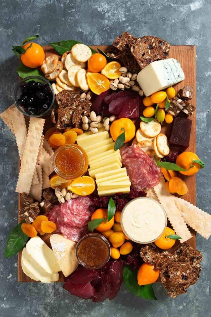 crackers, meat, cheese, jams, nuts, dried fruit on a large wooden cutting board