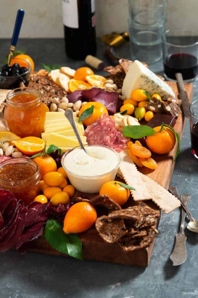 A cheese board filled with citrus, bresaola, goat cheese, crackers, etc. with a bottle of wine behind it.